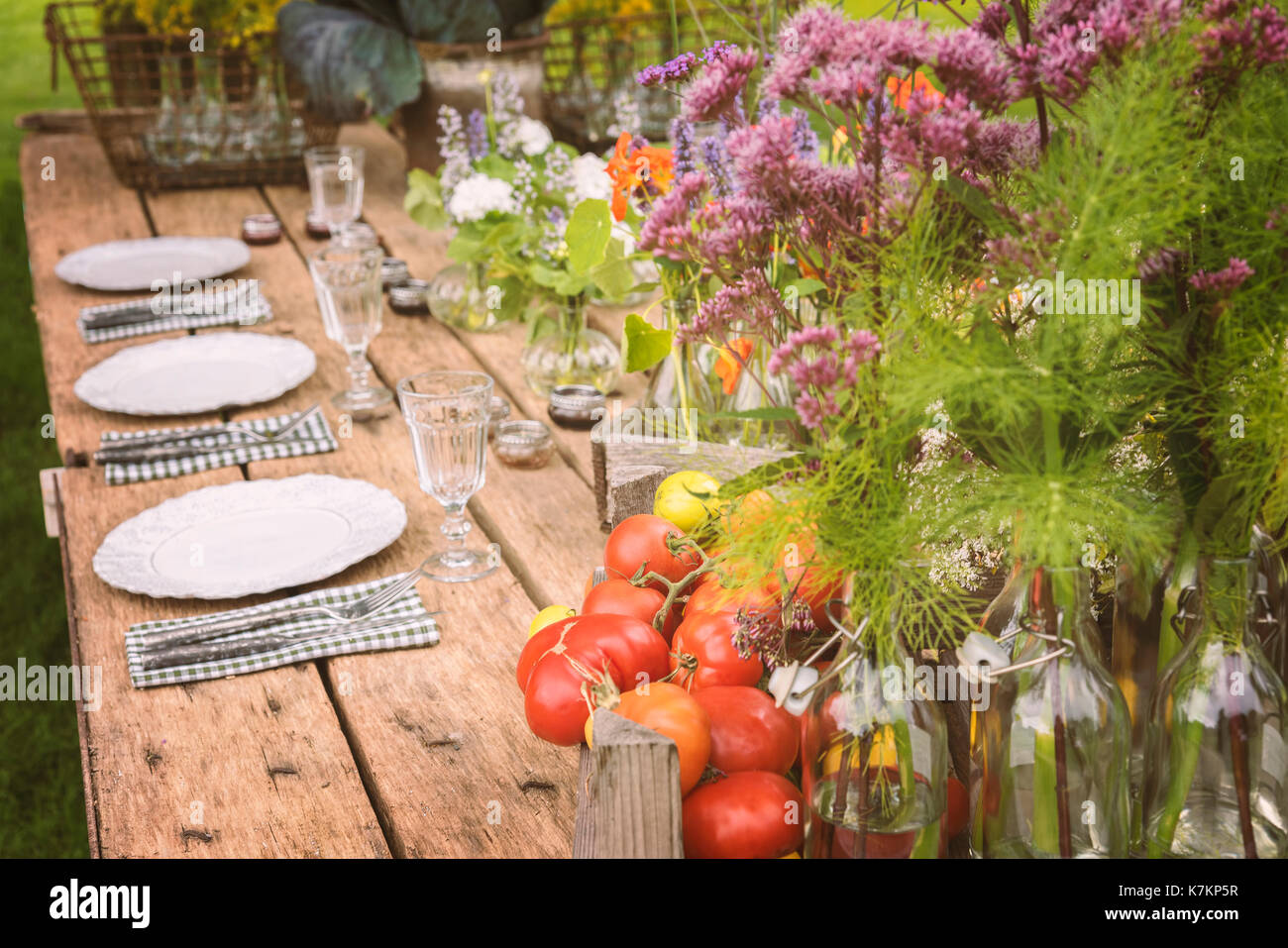 Wooden table setup for garden party or dinner reception. - Stock Image