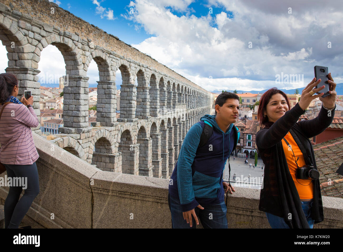 Tourists taking selfie photographs with smartphone at famous spectacular Roman aqueduct, Segovia, Spain - Stock Image