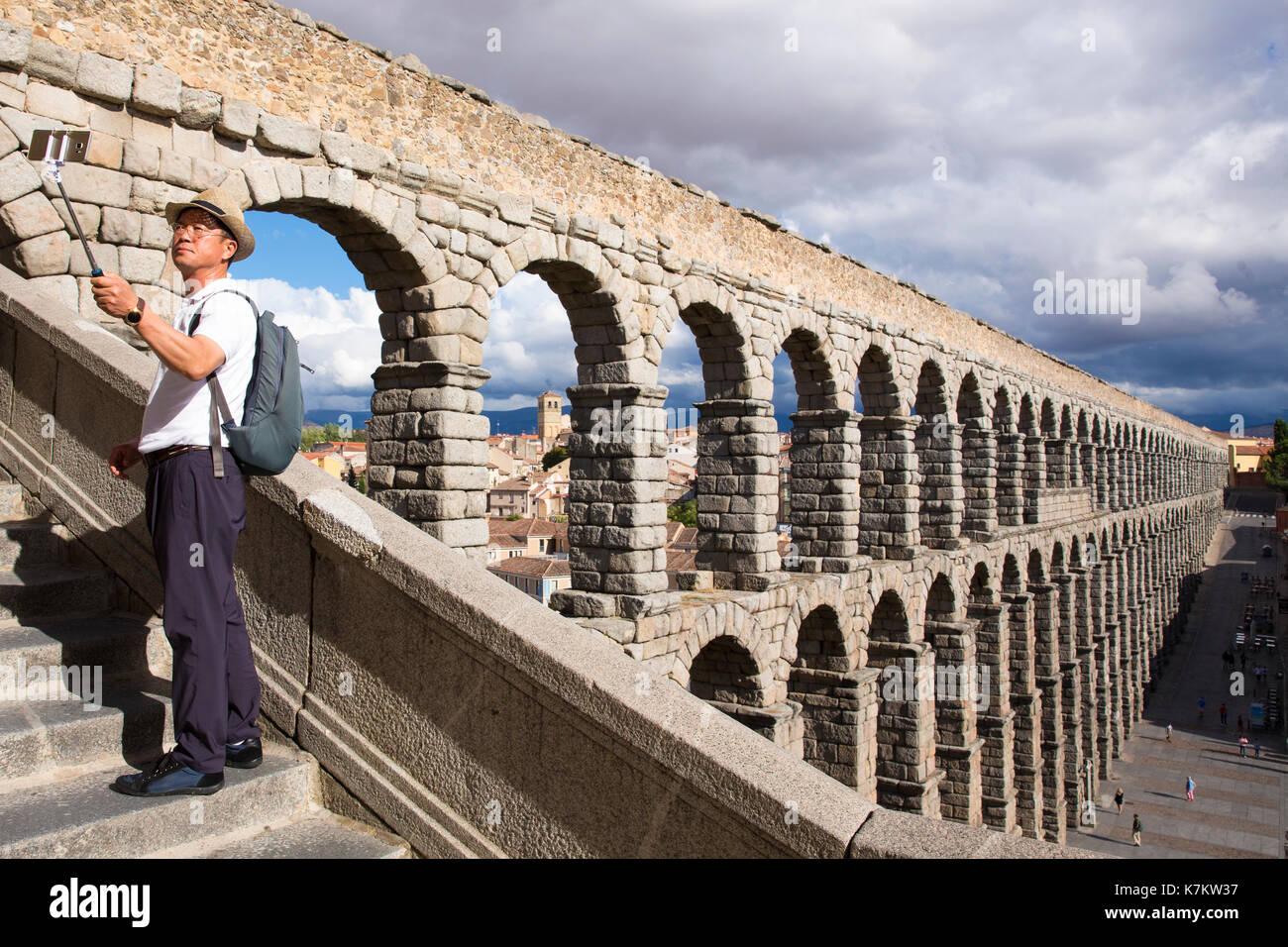 Tourist taking selfie photographs with smartphone on selfie stick at famous spectacular Roman aqueduct, Segovia, - Stock Image