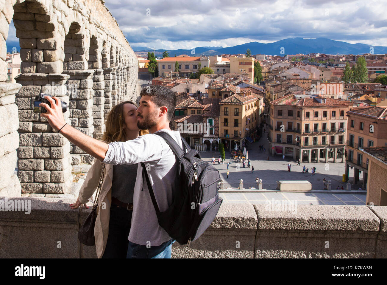 Tourist couple taking selfie photographs with SLR camera at famous spectacular Roman aqueduct, Segovia, Spain - Stock Image