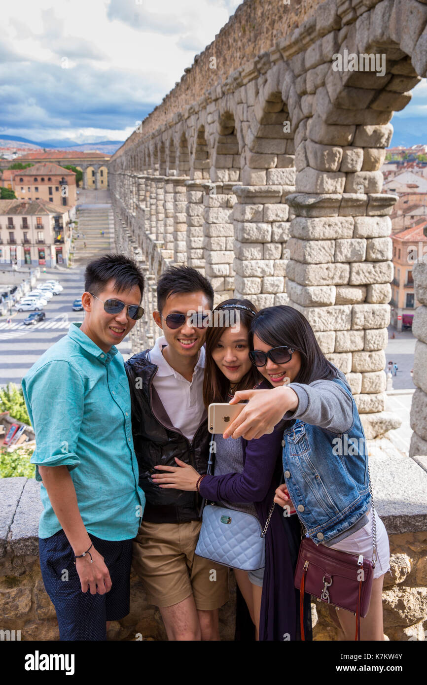 Young Chinese tourists taking selfie photographs with iPhone smartphone at famous Roman aqueduct, Segovia, Spain Stock Photo