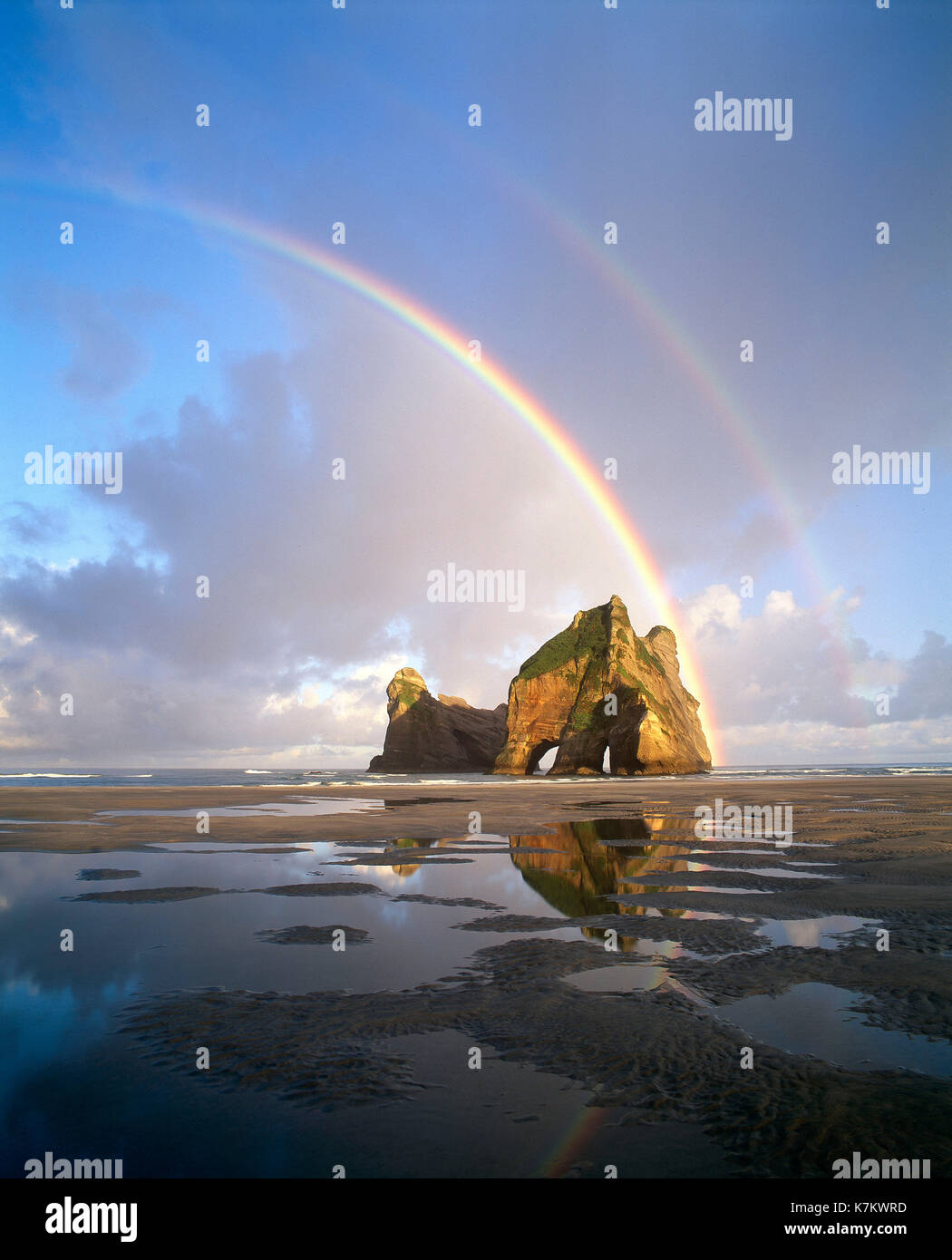 New Zealand. Rainbow over 'Farewell Spit' beach and Rock Arch. South Island. - Stock Image