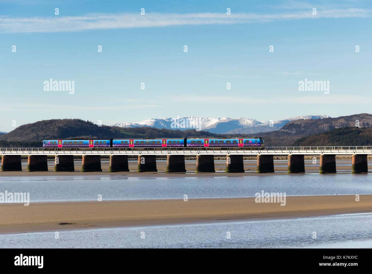 A First TransPennine Express Class 185 diesel multiple unit passenger train crossing Arnside railway viaduct over the river Kent - Stock Image