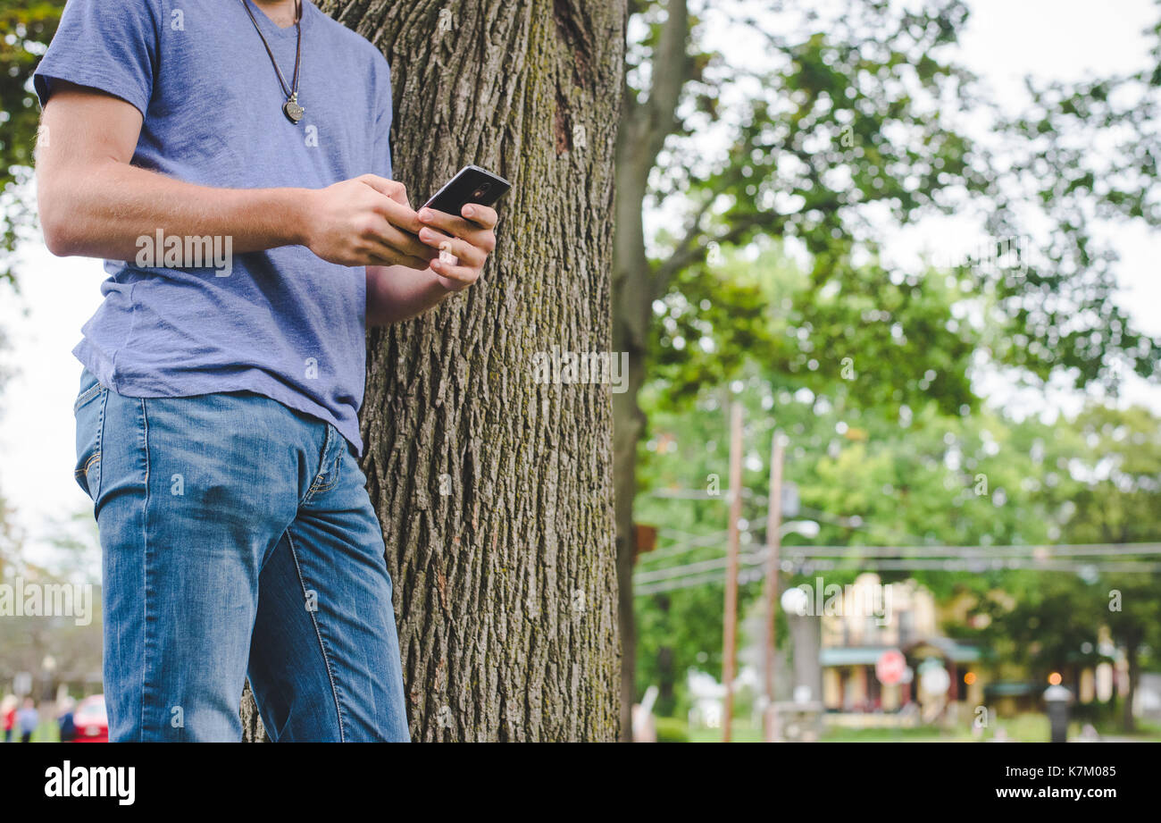 A young man looks at his cellphone while leaning against a tree. - Stock Image