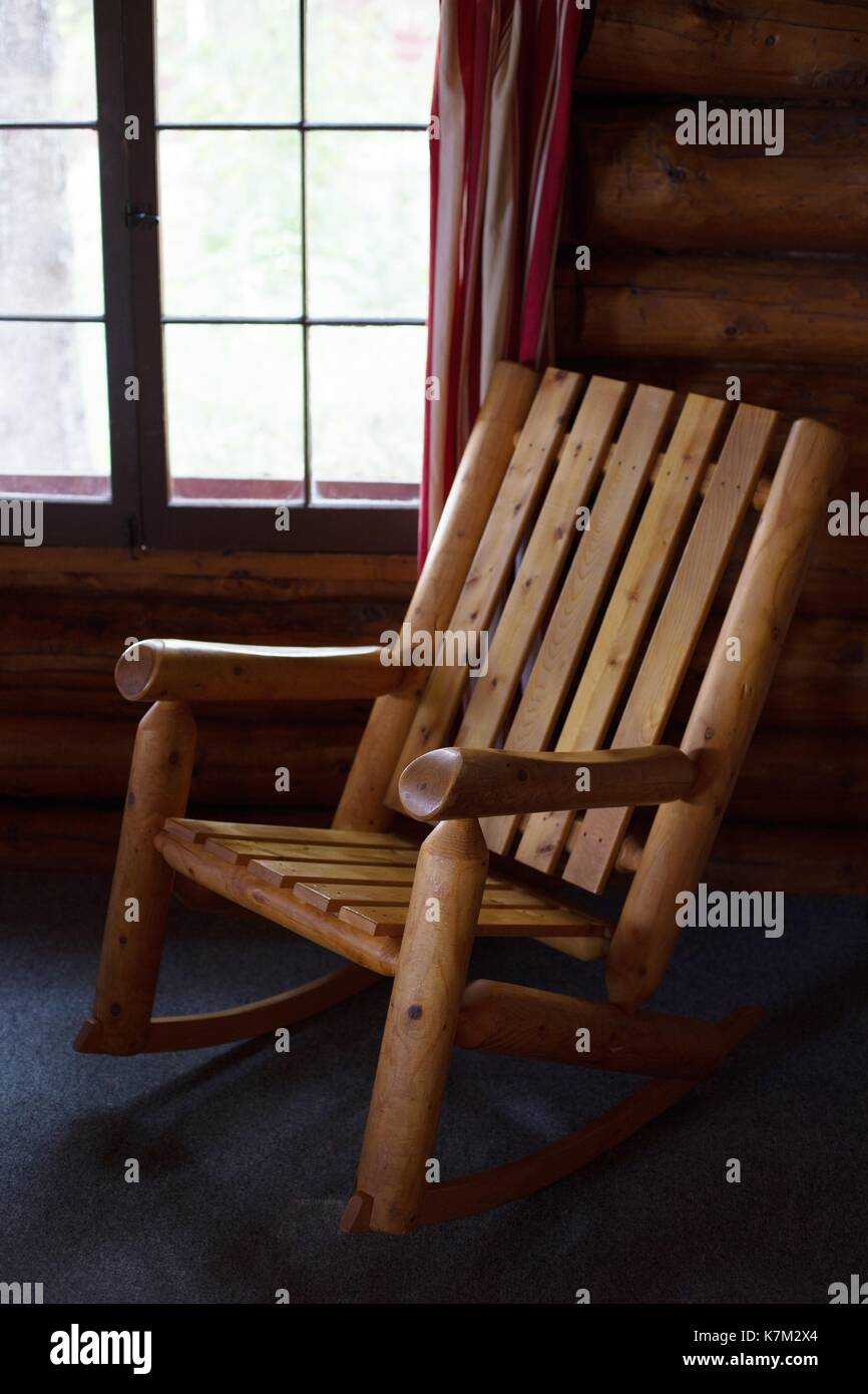 An Old Fashioned Wooden Rocking Chair In A Log Cabin.