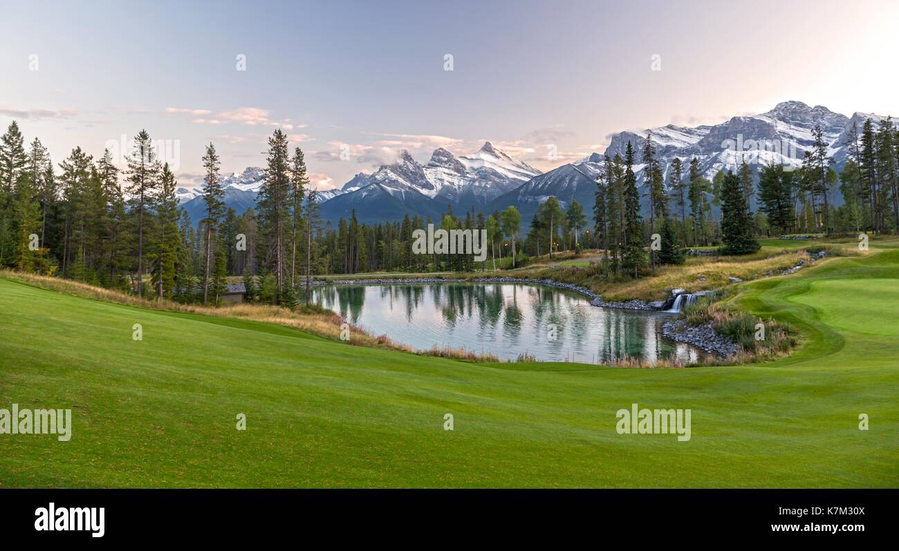 Silvertip Golf Course Green and Distant Landscape View of Three Sisters Snowy Mountain Tops above Town of Canmore in Foothills of Rocky Mountains Albe - Stock Image