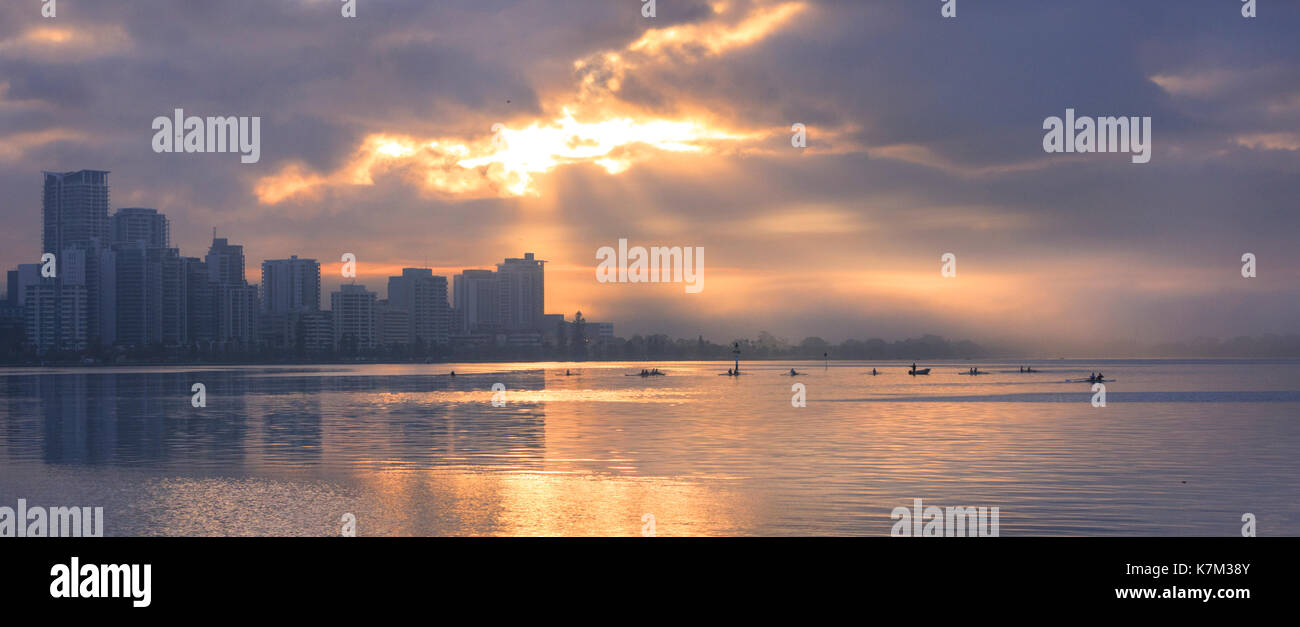 A university rowing club on the Swan River at sunrise. - Stock Image
