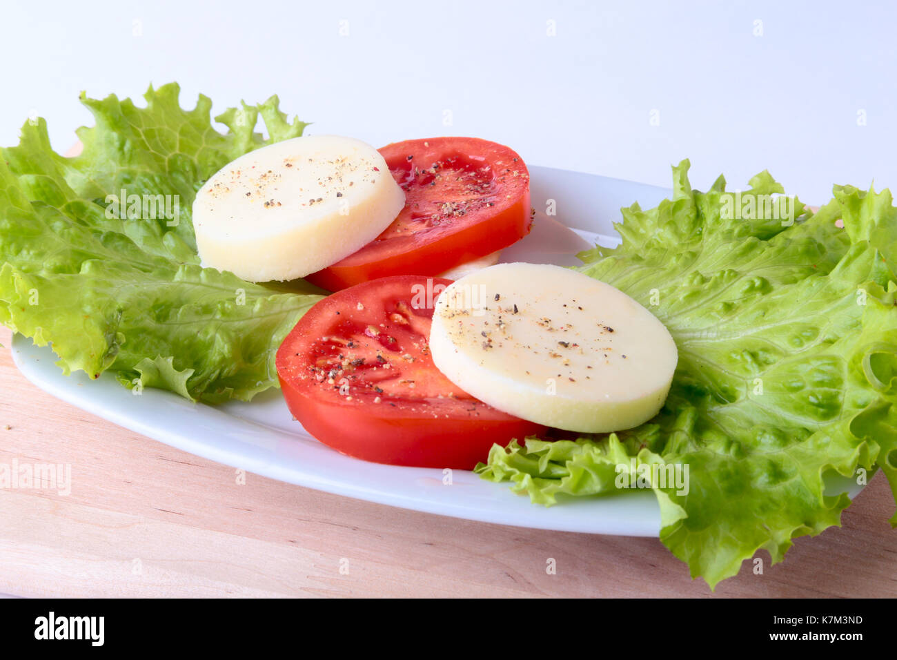 Portion of Mozzarella with Tomatoes, lettuce leaf and Balsamic dressing on white plate. selective focus close-up shot. - Stock Image