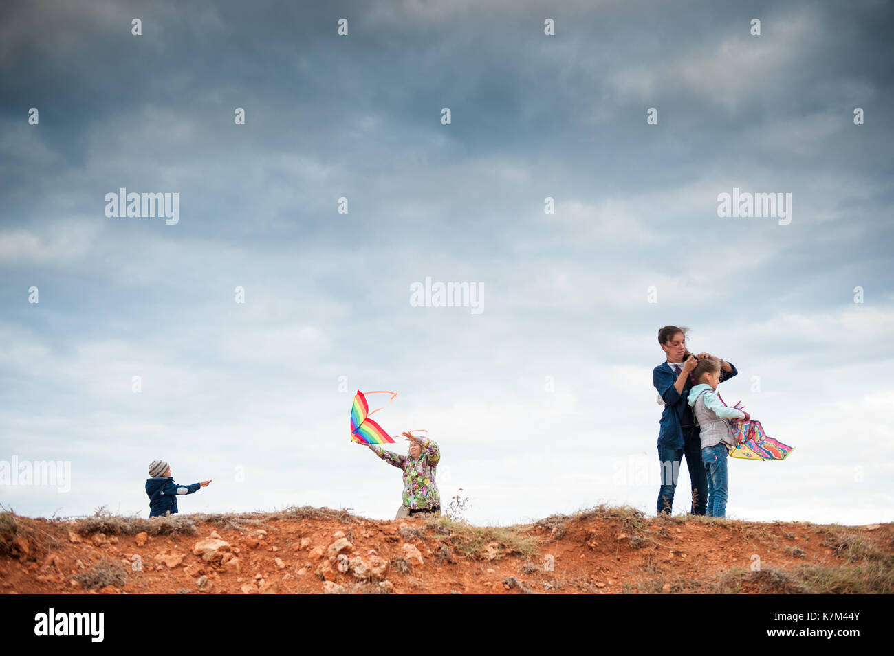 happy family of three generations playing with kites outdoor - Stock Image