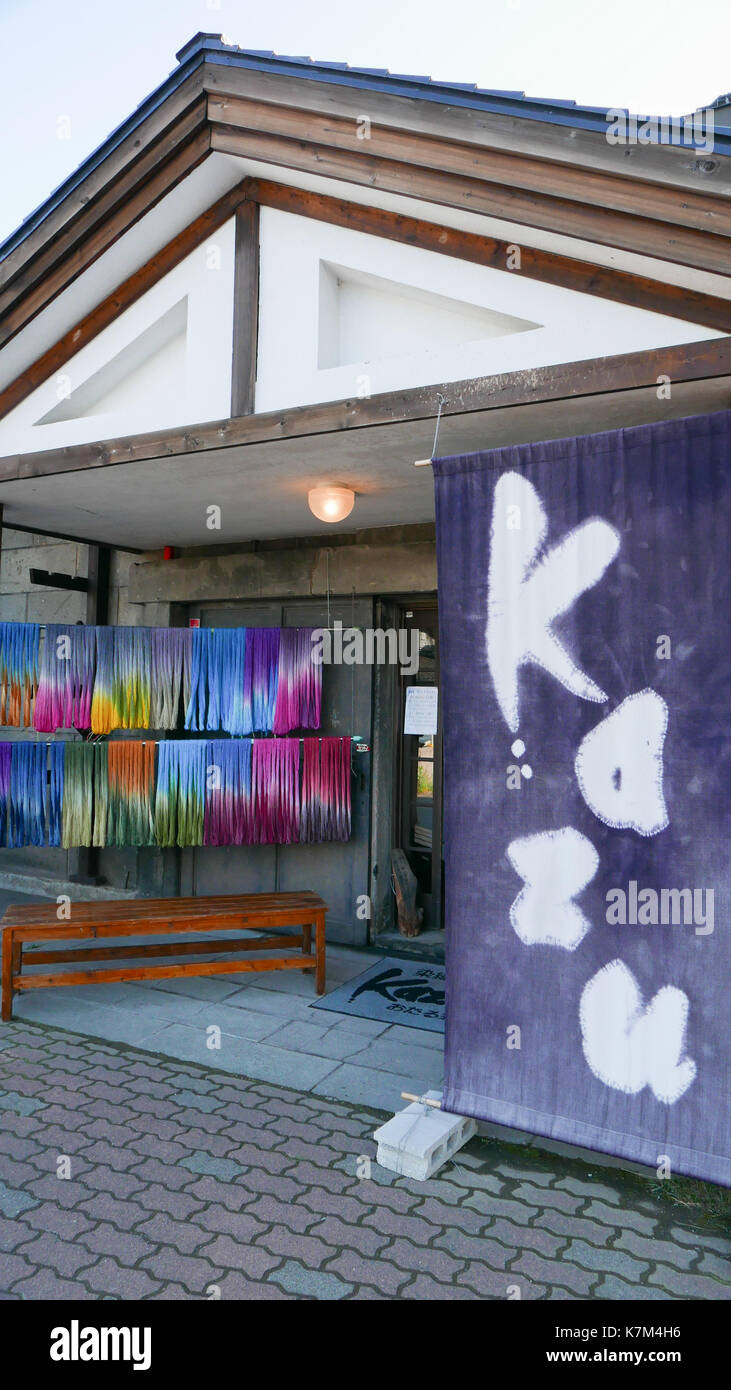 Kazu traditional Japanese blue and white fabric sign in front of shop with examples of dyed multicolored string above bench for shoppers to rest. - Stock Image