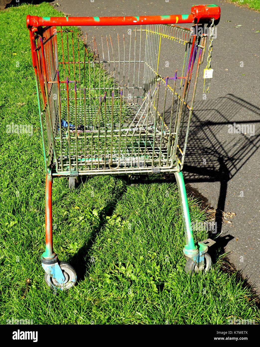 Supermarket trolley, dumped and broken. - Stock Image