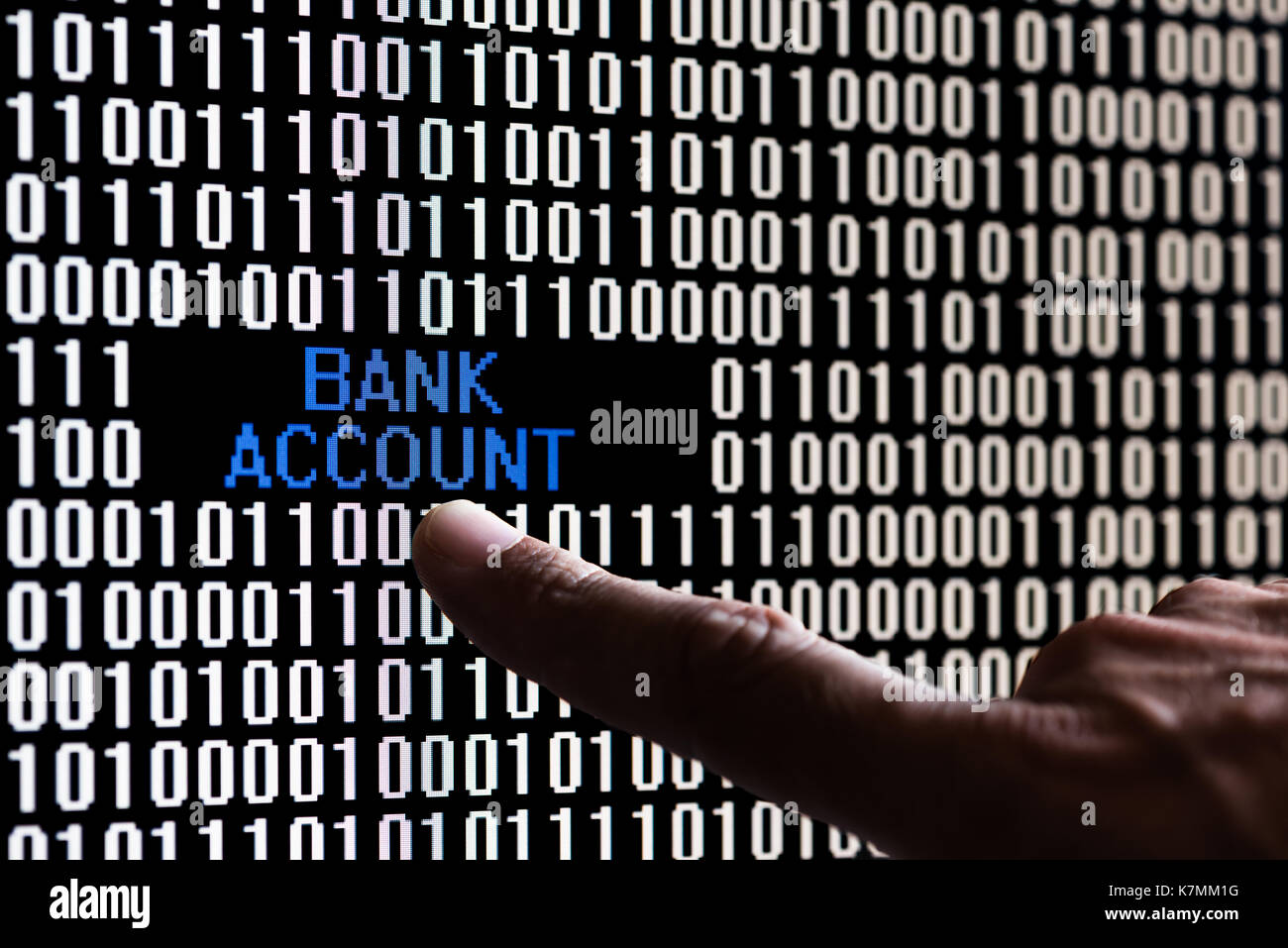 Finger pointing bank account data in binary code - Stock Image