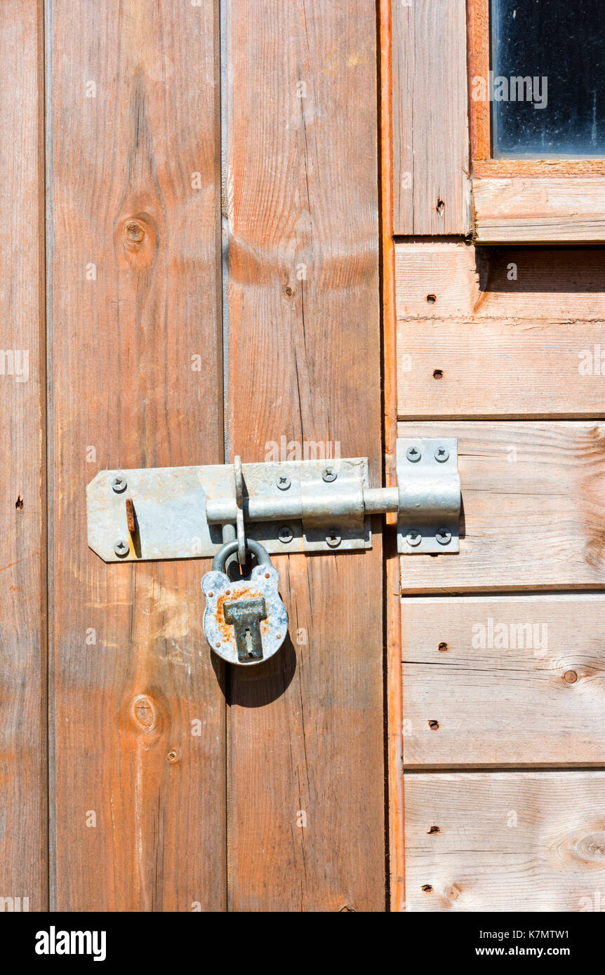 Large metal bolt and padlock on a wooden shed door Stock Photo