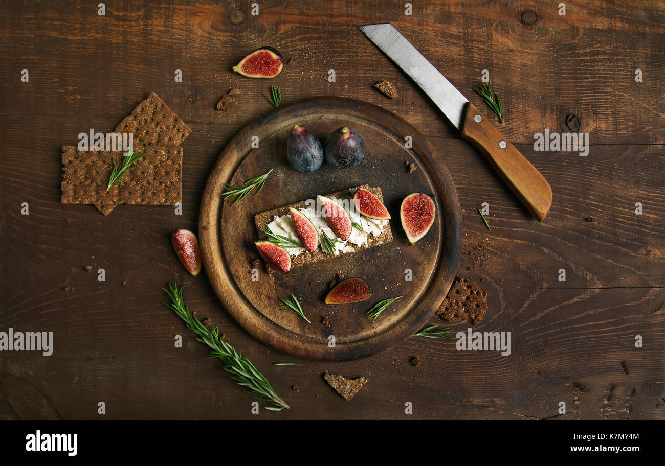 Small loaf of bread with cake cheese, figs and rosemary on the table - Stock Image