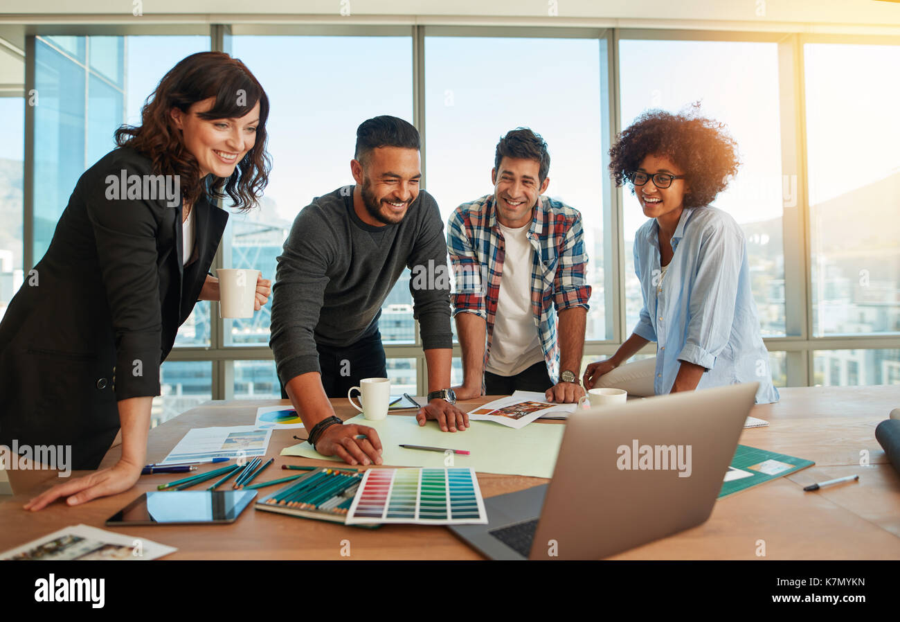 Young man discussing new designs and color scheme with colleagues in a meeting. Team of young professionals having - Stock Image