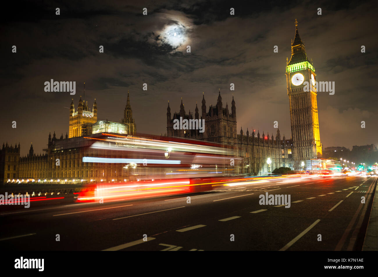 Palace of Westminster with Big Ben at night, red double-decker bus on the Westminster Bridge, motion blur, London, England - Stock Image