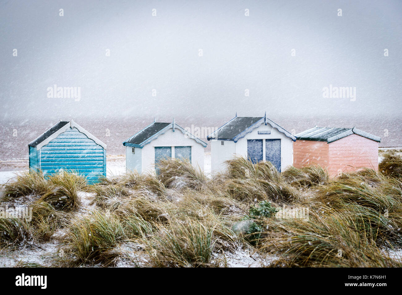 The beach huts at Southwold, Suffolk, UK in a show shower in January - Stock Image