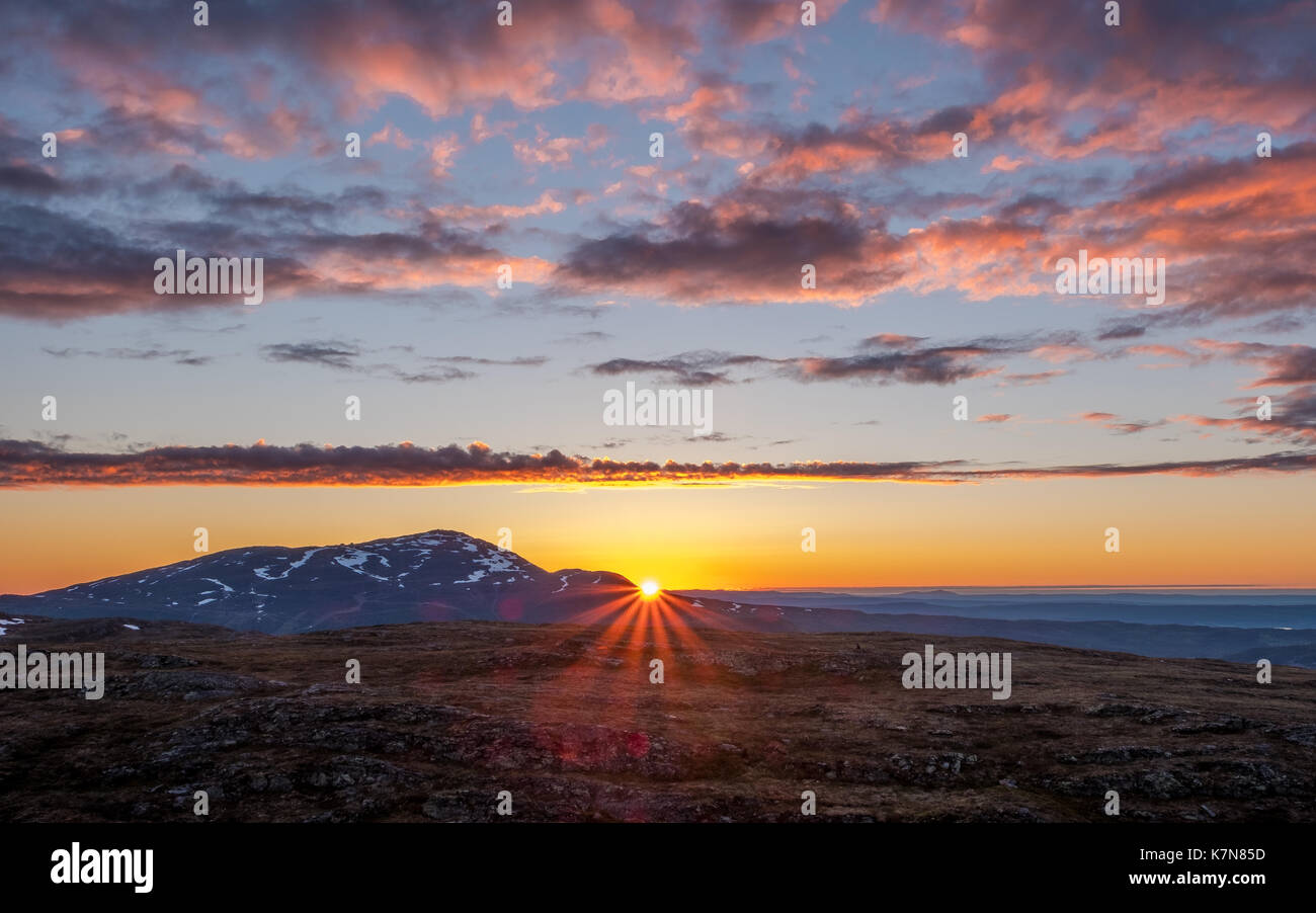 Sun beams peeking over mountain at sunrise - Stock Image