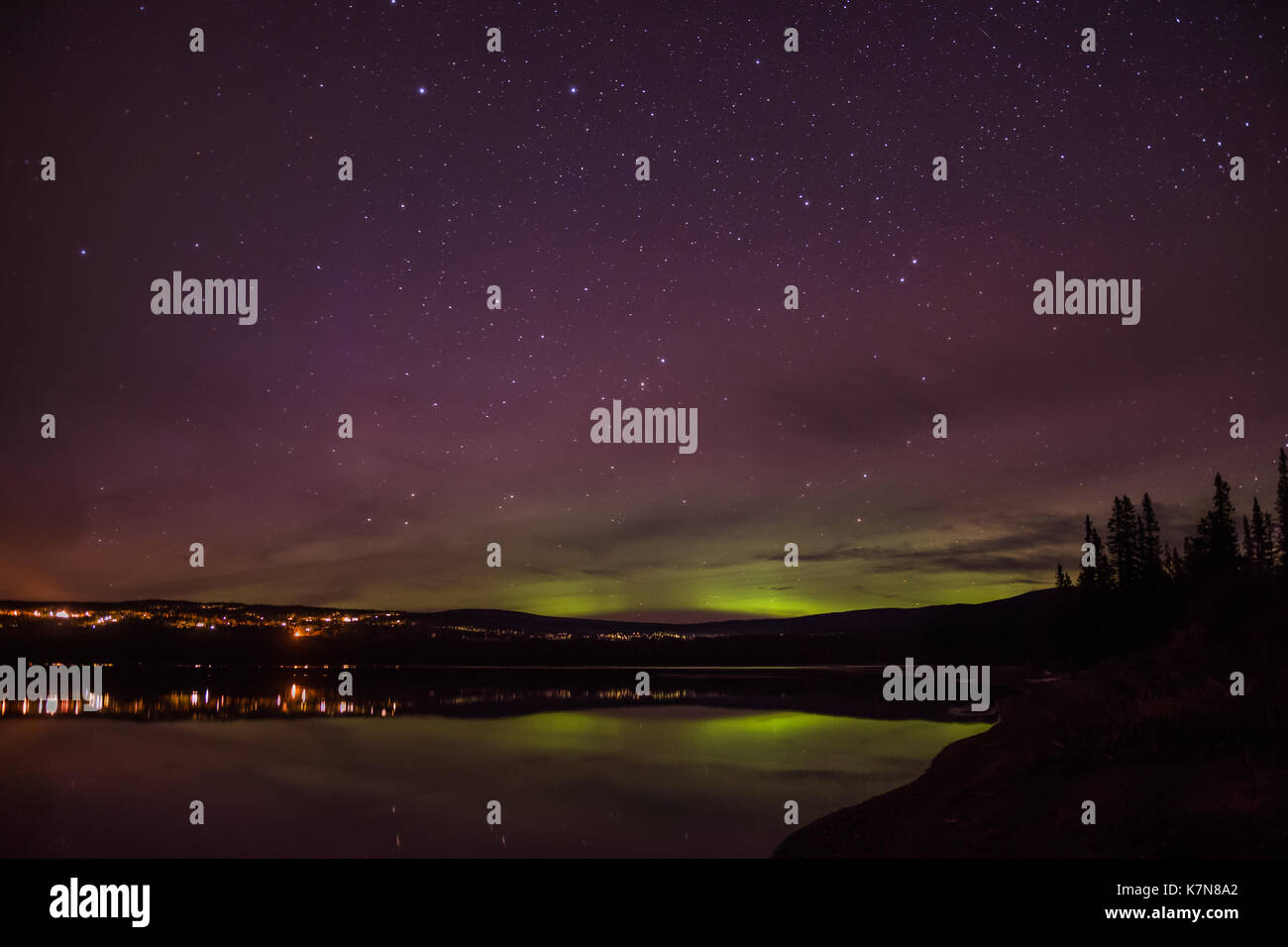 Aurora borealis lights dancing over village and lake - Stock Image