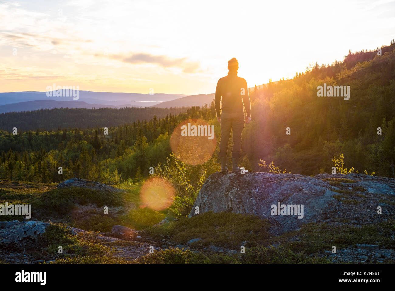 Young man standing on big stone looking into the sunset amidst scenery - Stock Image