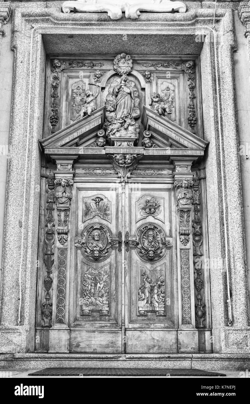 Carved wooden portal of an italian church. - Stock Image