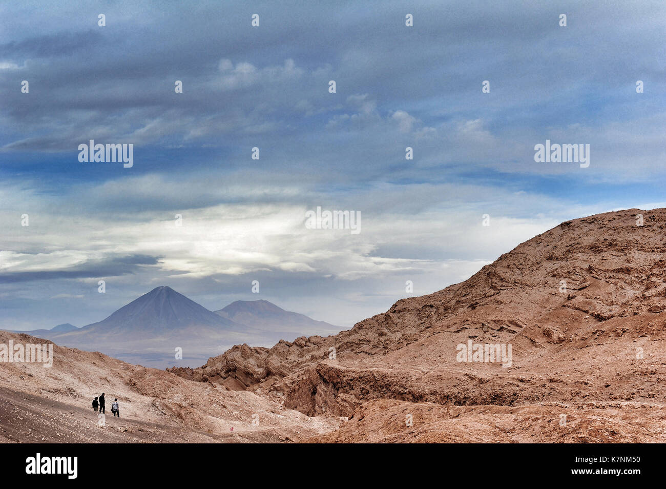 Three people in the Valle de la Luna, Chile. In the background, the peak of the Licancabur volcano. Stock Photo