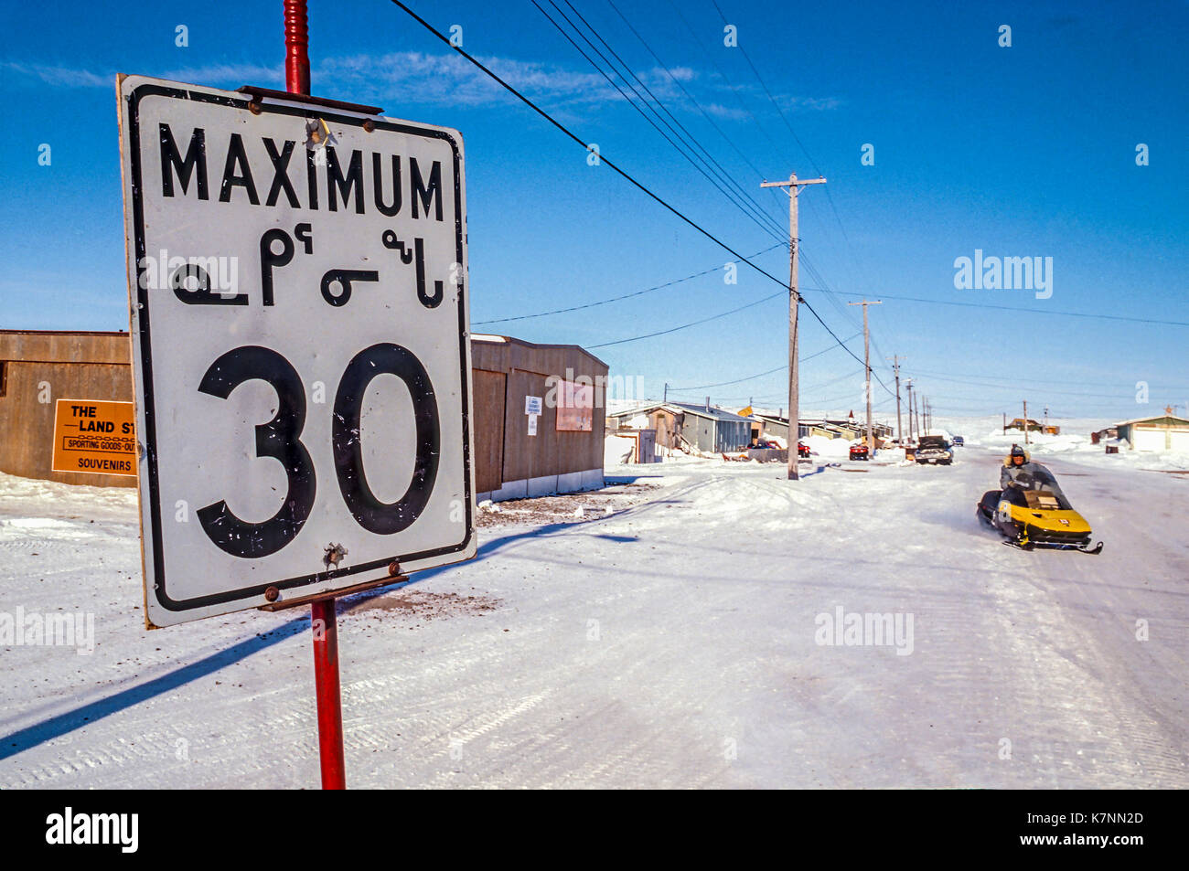 Speed limit sign in Inuit language Inuktitut) along a snowy street in Baker Lake, Nunavut, Canada. - Stock Image