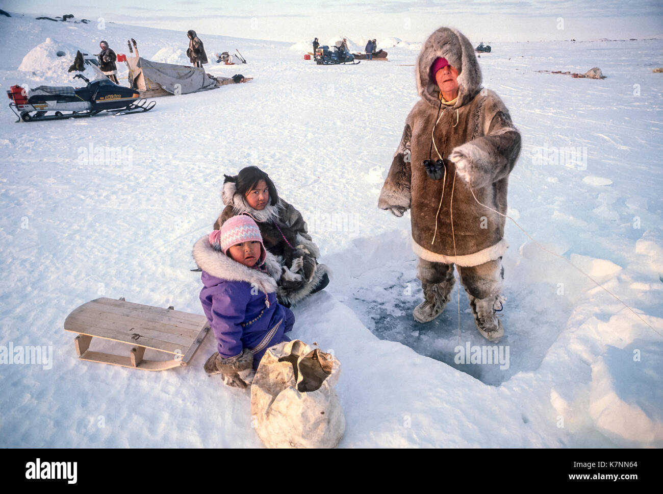 Inuit girls, ages 4 and 11, along with visitor, by fishing hole. Everyone except the younger girl, including other visitors and Inuit elders in background, are dressed in traditional caribou skin clothing. Outside Baker Lake, Nunavut, Canada. - Stock Image