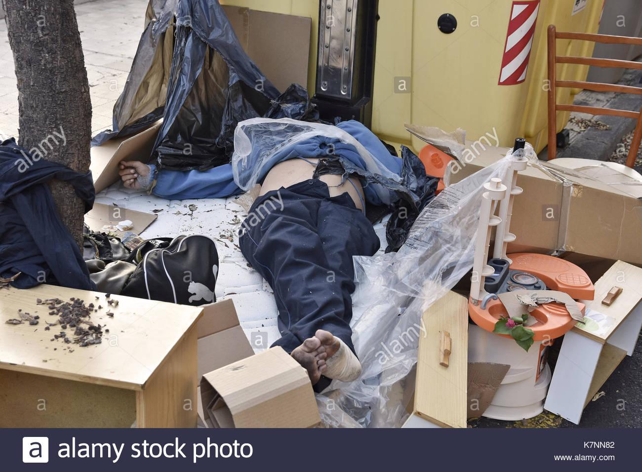 Man sleeping on the mattress beside rubbish bin in Santa Cruz de Tenerife Canary Islands Spain. - Stock Image