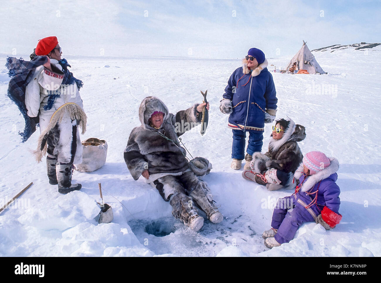 Visitor dressed in traditional caribou clothing, tries her hand at fishing in camp outside Baker Lake, Nunavut, Canada. Inuit elders and Inuit children are gathered around the fishing hole. - Stock Image