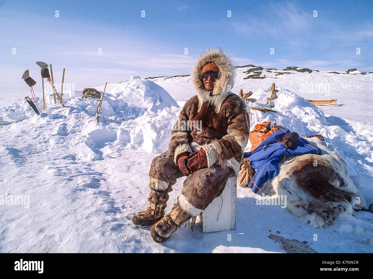 Inuit elder, 60s, dressed in traditional caribou skin clothing, rests outside his igloo, seen behind him with tools and boots set out to air out. - Stock Image