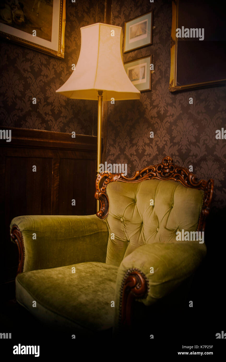 Image of an old comfy armchair in period lounge with a standard lamp and atmospheric lighting - Stock Image