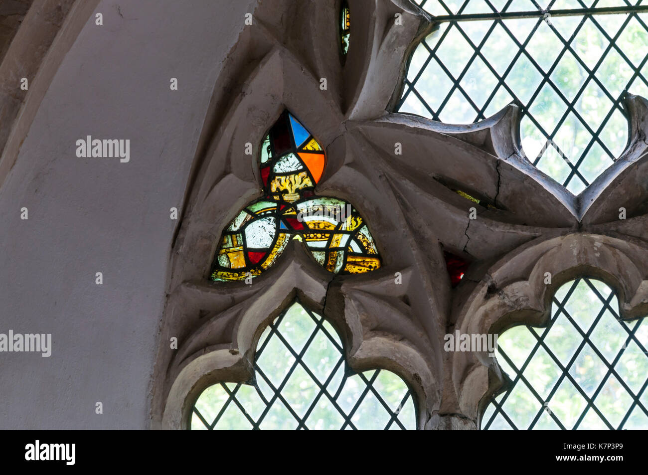 Fragments of medieval stained glass in 14th century reticulated tracery window at St Peter & St Paul church, Newchurch on Romney Marsh, Kent. - Stock Image