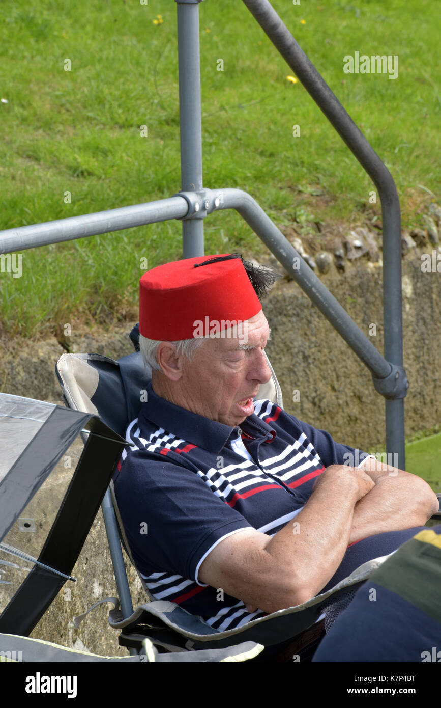 an older or elderly man taking a cat nap or sleep in a folding chair out of doors wearing a fez hat with a tassle and his arms folded. Snoozing, tired - Stock Image