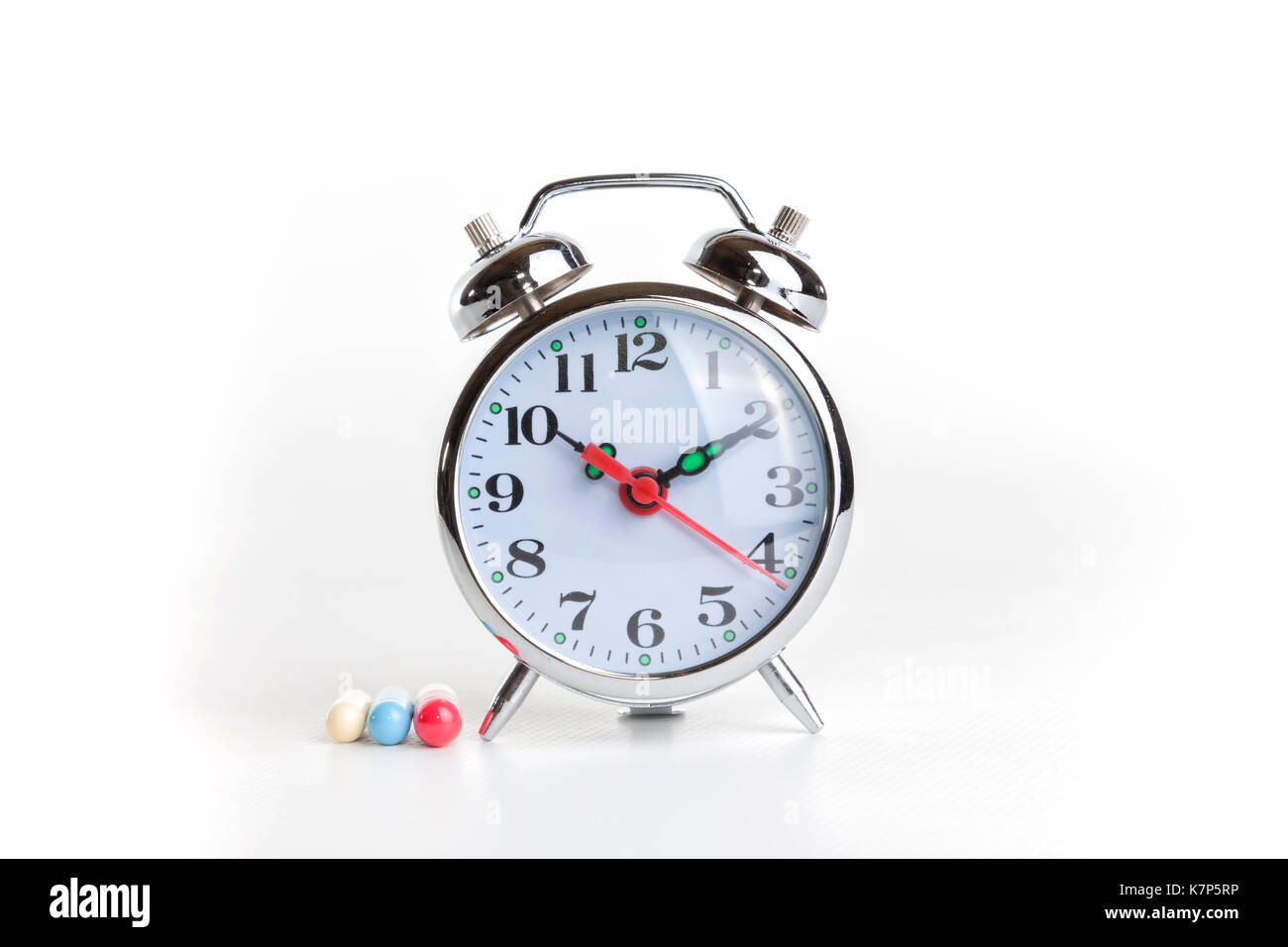 Medicines and alarm clock on white background. - Stock Image