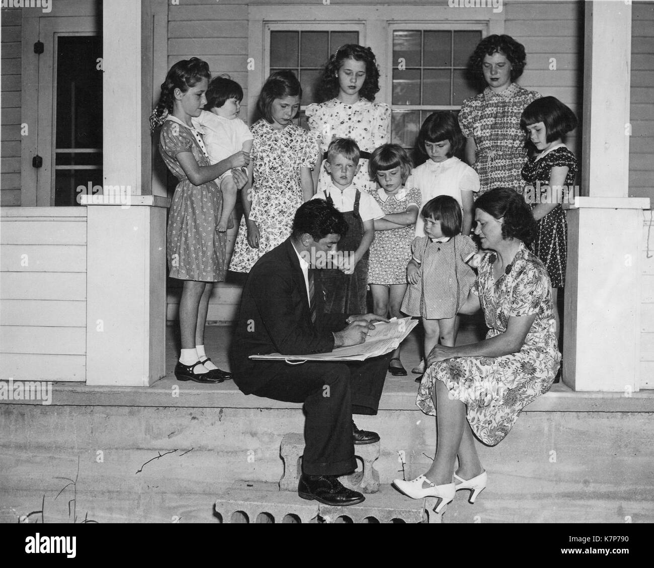 Male enumerator counts a large family of nine girls and one boy for the 1940 Census, 1940. - Stock Image
