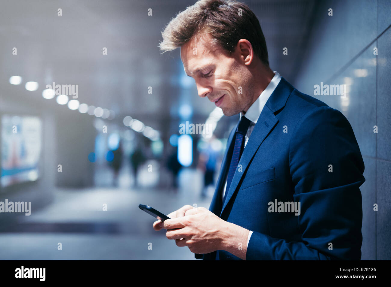 Smiling young businessman standing on a subway platform during his morning commute reading text messages on his cellphone - Stock Image