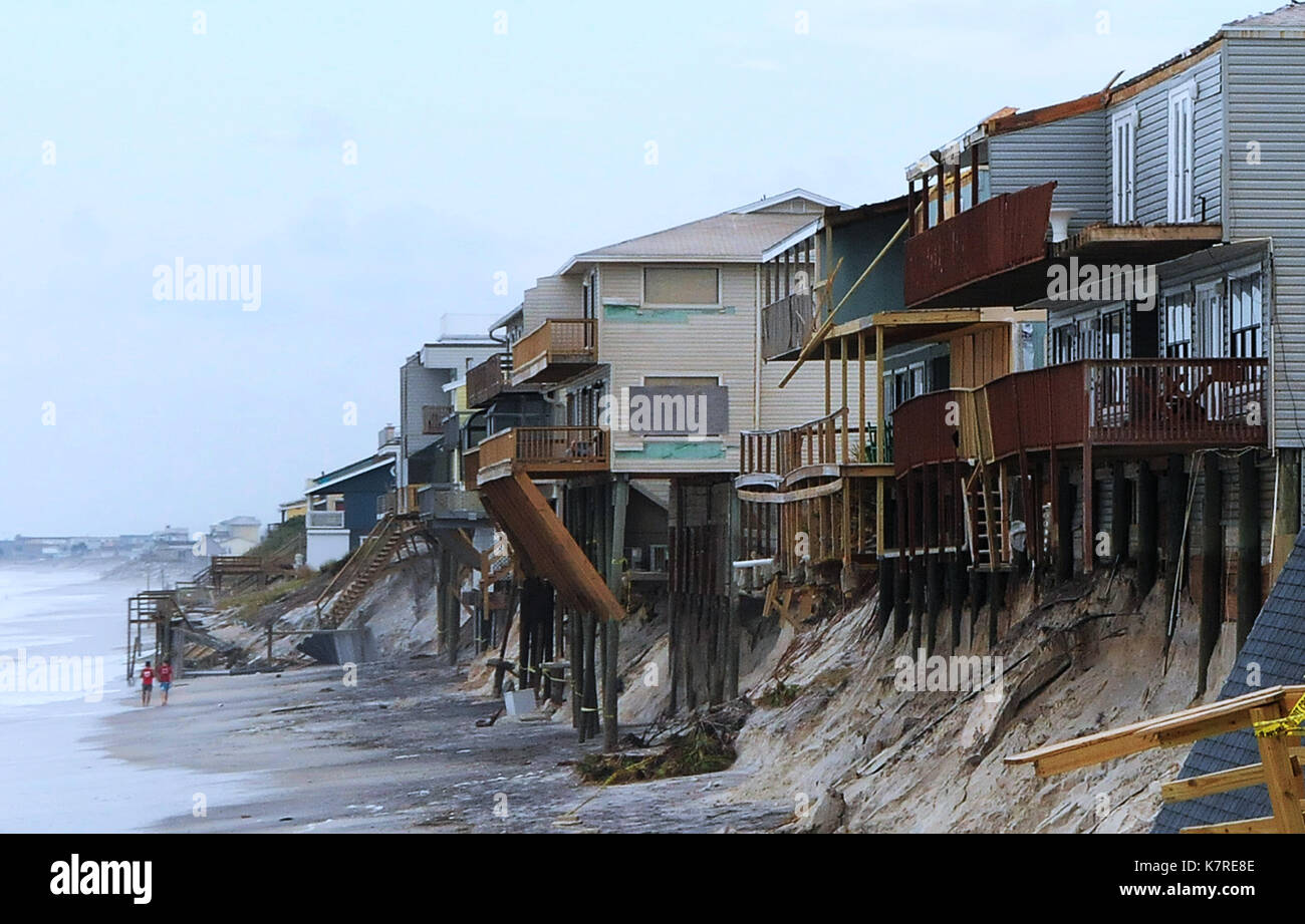 September 16, 2017- South Ponte Vedra Beach, Florida, United States - People walk the beach past beachfront homes on the verge of falling into the Atlantic Ocean due to beach erosion caused by Hurricane Irma on September 11, 2017 in South Ponte Vedra Beach, Florida. (Paul Hennessy/Alamy) - Stock Image