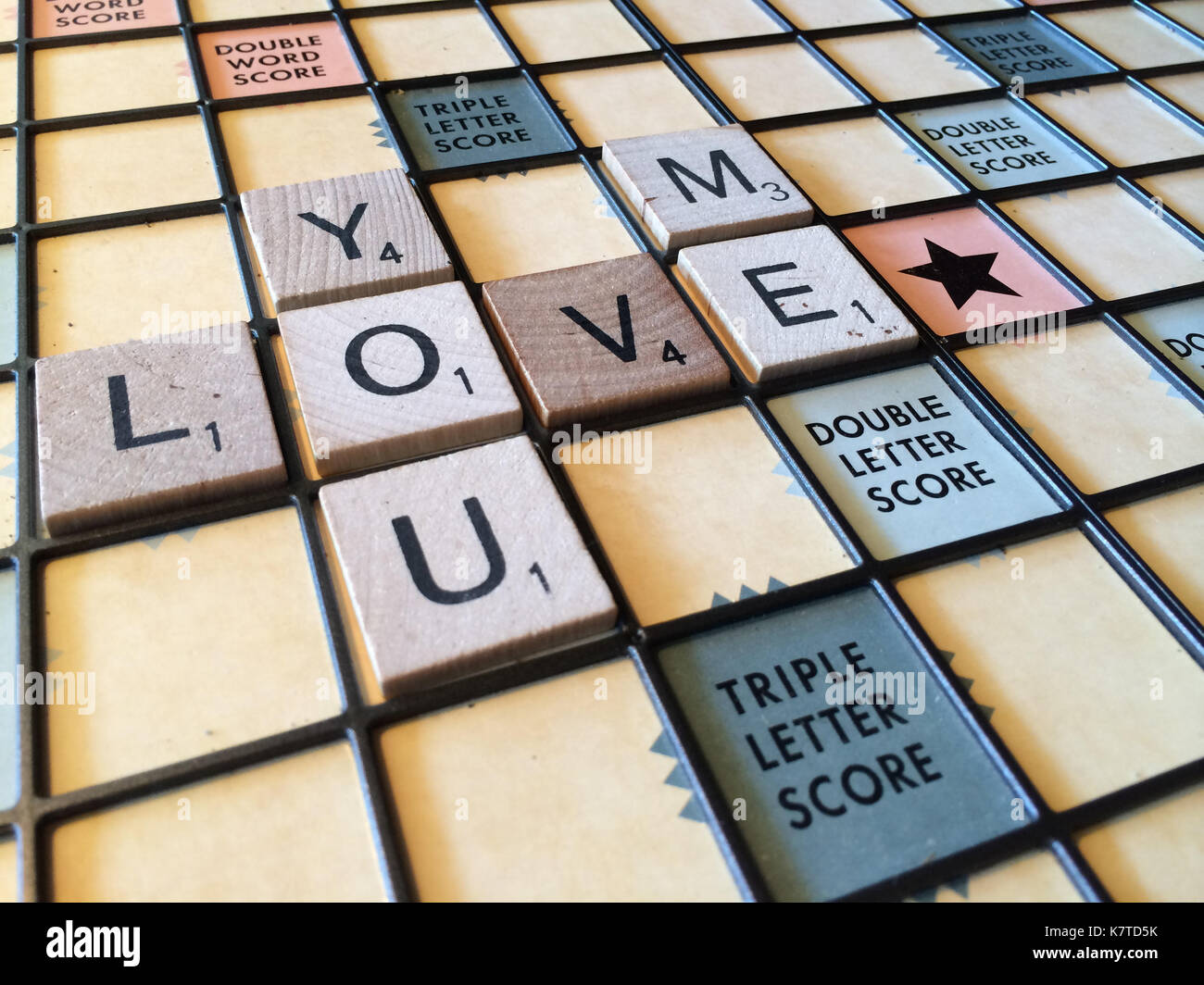 The words 'you love me' spelled out on a Scrabble game board. - Stock Image