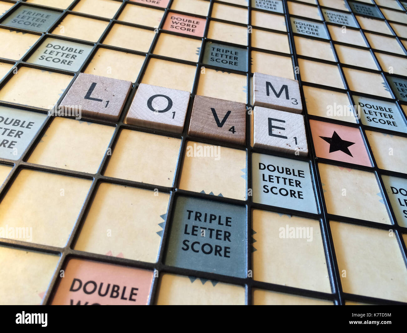 The words 'love me' spelled out on a Scrabble game board - Stock Image