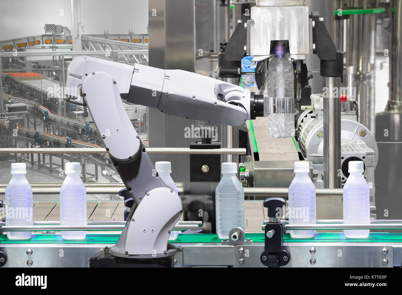 Robotic arm holding water bottles on drink production line in factory, Industry 4.0 concept - Stock Image