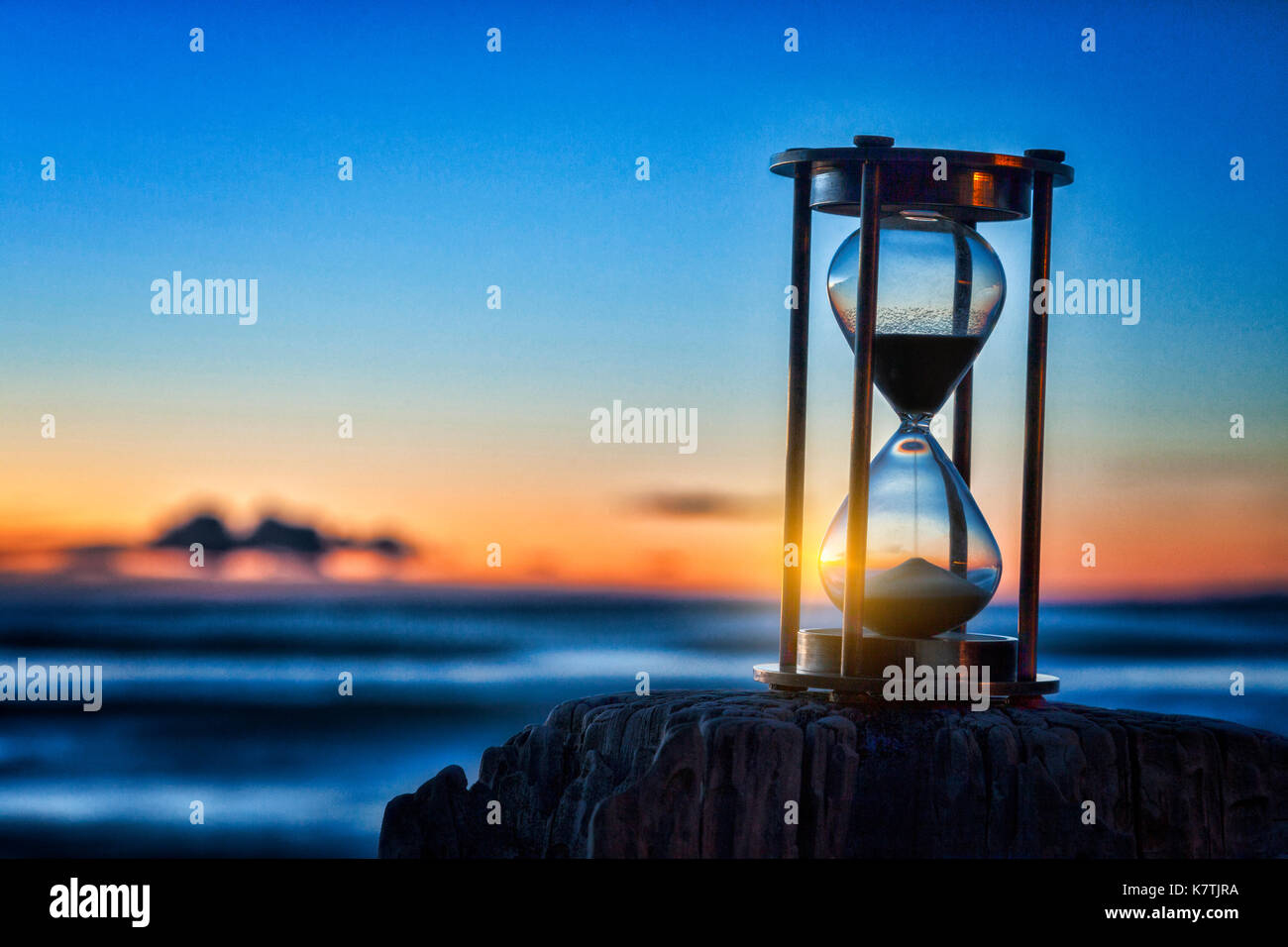 Hourglass or sand timer in front of a beatiful clear sunrise or sunset. - Stock Image