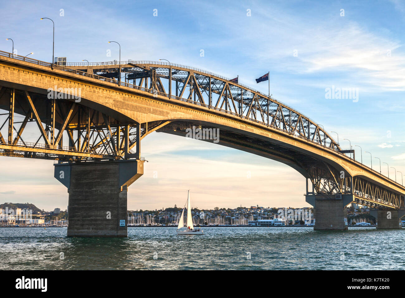 Auckland Harbour Bridge in evening light with yacht passing under. - Stock Image