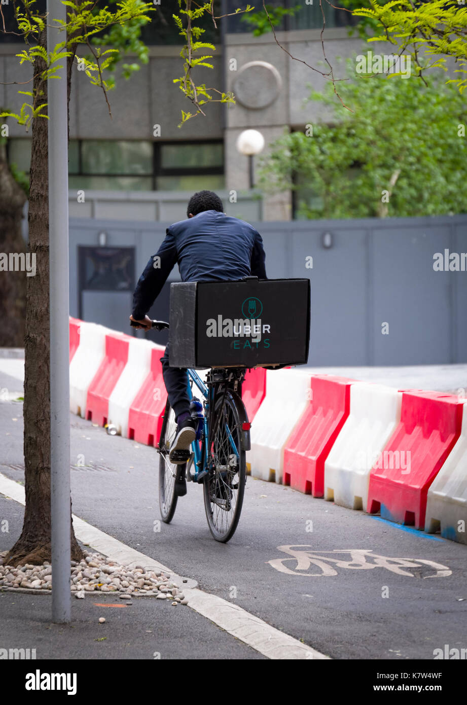 UberEATS cycle delivery courier in London, Ubereats is a take away food service which can be ordered from a Smartphone Stock Photo