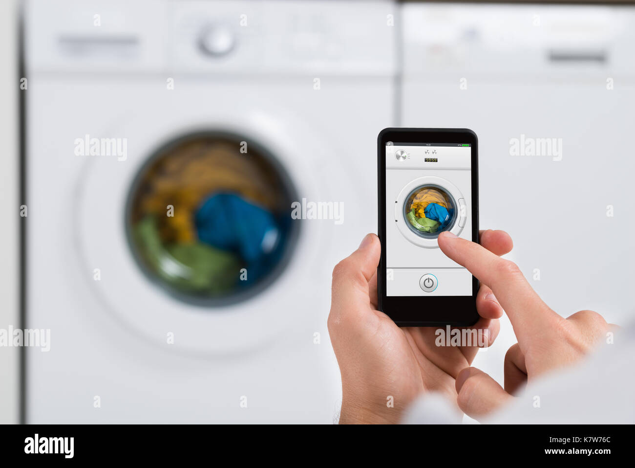 Close-up Of Person Hands Using Mobile Phone To Operate Washing Machine Appliance At Home - Stock Image