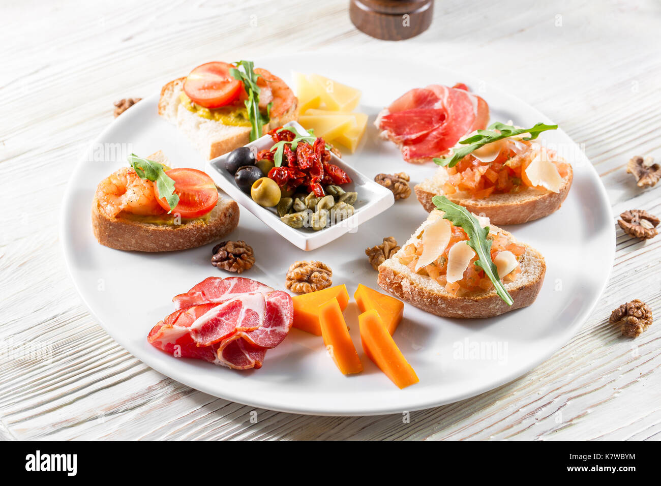 Selection of tasty bruschetta or canapes on taosted baguette and quark cheese topped with smoked salmon, shrimp. - Stock Image
