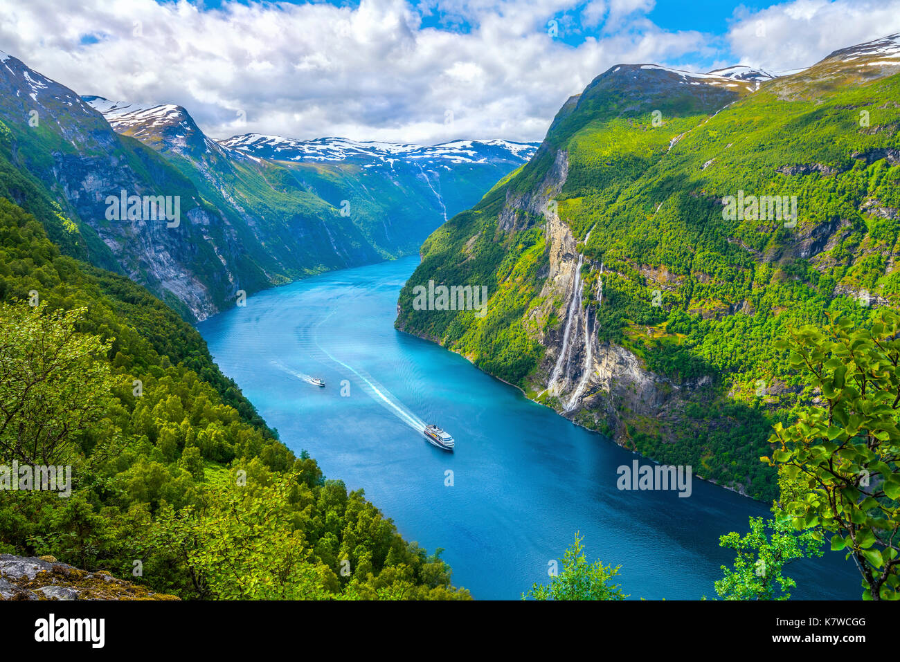 cruise ship of Hurtigruten and the ferry passing Seven Sisters waterfall in the Geirangerfjorden, view from above, mountain panorama, Norway - Stock Image