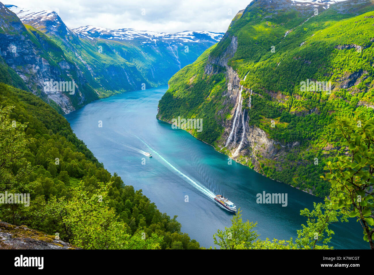 view to the Seven Sisters waterfall and the Geirangerfjorden with a cruise ship of Hurtigruten and a ferry, mountain panorama, Norway - Stock Image
