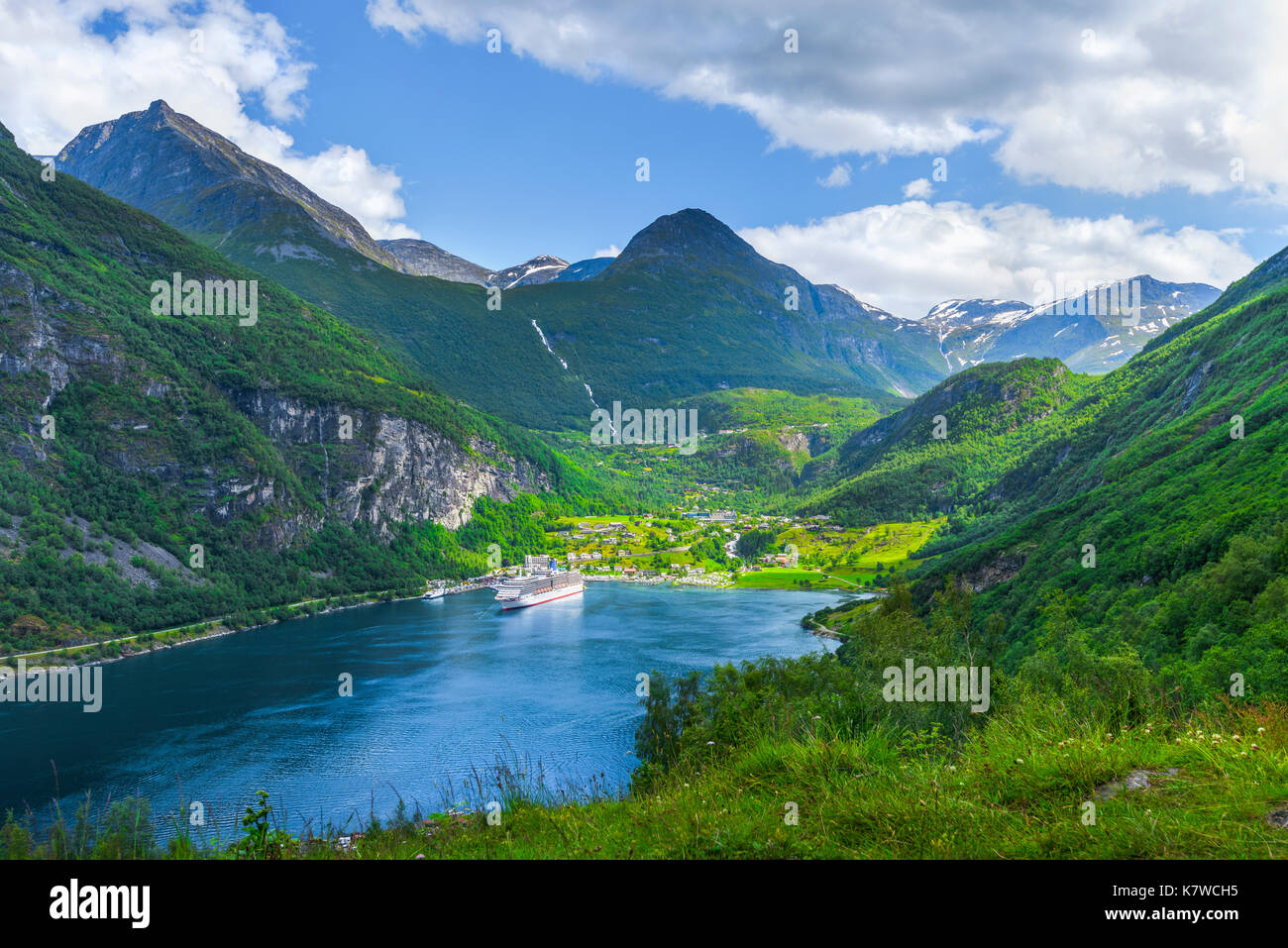 a cruise ship anchoring in the bay of Geiranger, panorama view, Geirangerfjorden, Norway - Stock Image