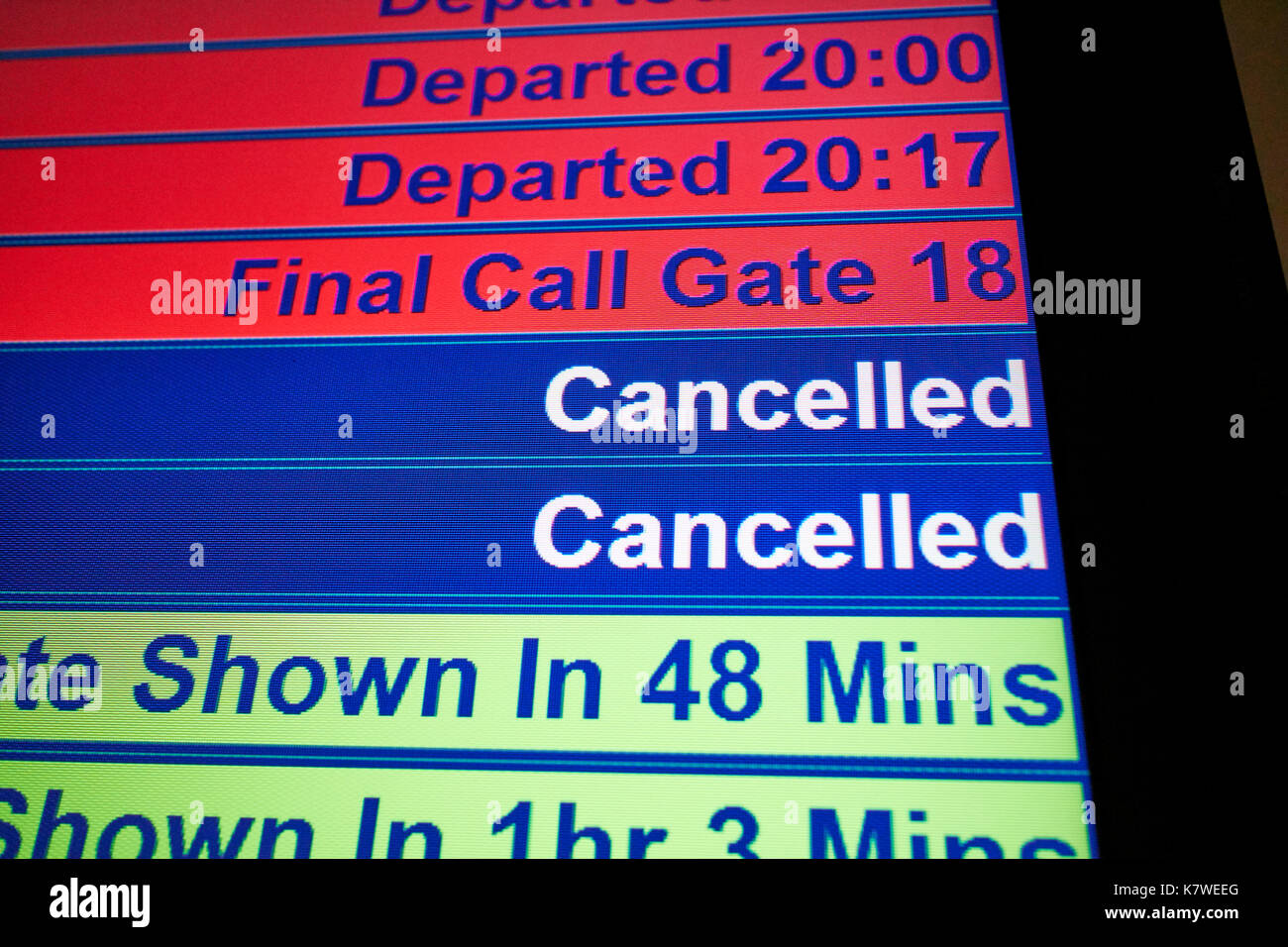 airport flight information screen showing departed, final call and cancelled flights - Stock Image